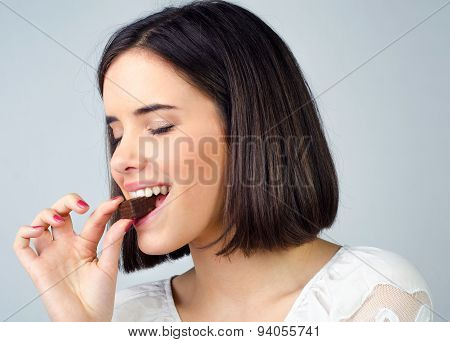 Portrait Of The Beautiful Girl Eating Chocolate Cookies Isolated On Gray Background