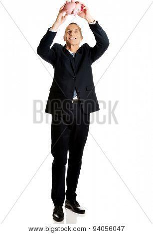 Full length cheerful businessman holding piggybank.