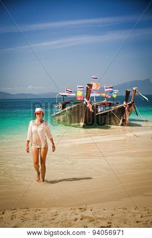 Woman walking on Tropical beach, longtail boats, Andaman Sea, Thailand