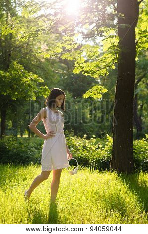 Beauitful Girl In White Dress And Small Basket Walking In Forest On Sunny Spring Day