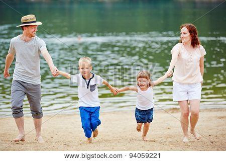 Content family with two children at beach running in summer