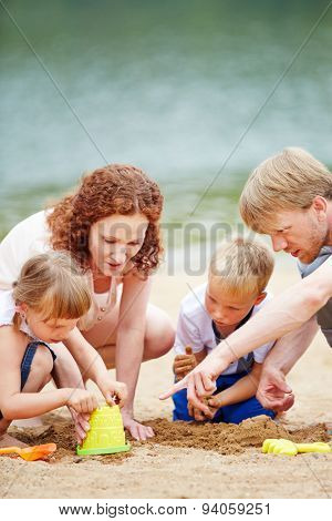 Family with two children playing on beach in summer