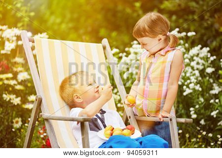 Two happy siblings eating fresh fruits in summer from a garden