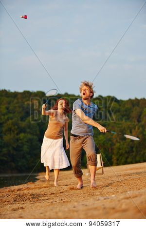 Sportive couple playing badminton together in summer at beach