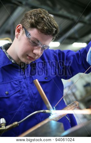 student in plumbing professional training, working on copper