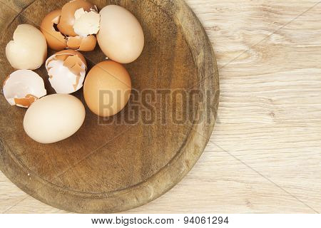 Whole eggs and shells lying on a wooden table. Preparing fried omelets.