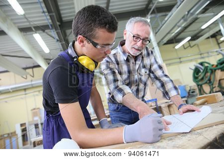 Carpenter with apprentice in training period