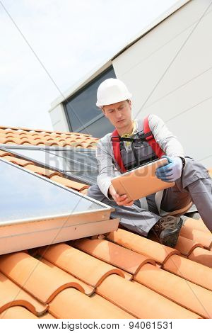 Man on roof top checking on solar panel installation