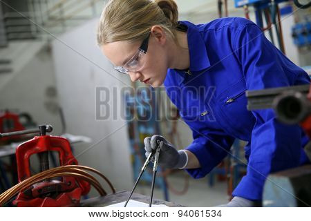 Young woman apprentice learning plumbing