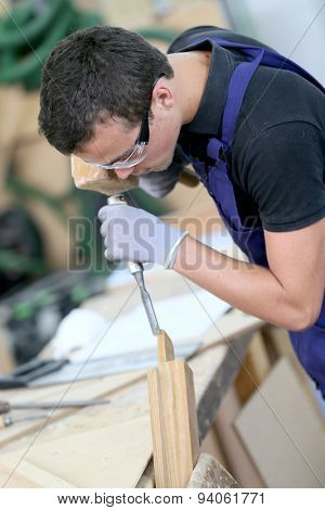 Young apprentice in carpentry working piece of wood