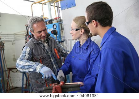 Students in plumbing listening to teacher's instructions