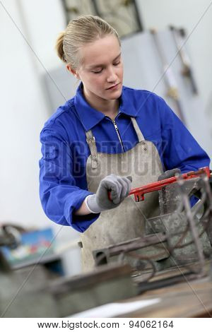 Young woman studying ironworks in professional school
