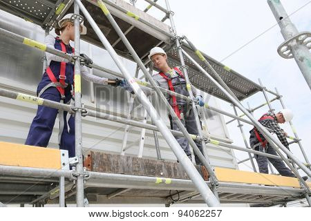 Construction workers installing scaffolding on site