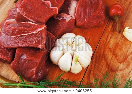 raw fresh beef meat fillet on a wooden plate with dill , hot green red peppers isolated over white background