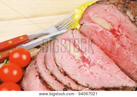 hot ham on wooden plate served over wood table