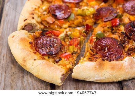 Delicious Baked Salami Pizza Served On Rustic Wooden Table