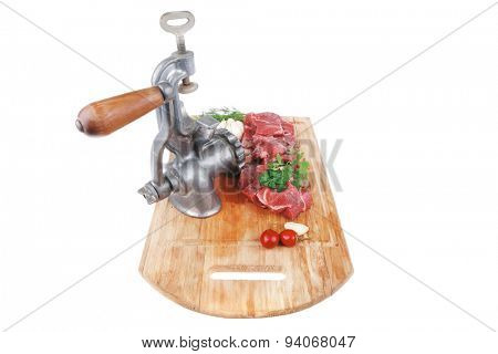 fresh raw beef meat slices over a wooden board with dill , green  and red hot peppers, and grinder isolated over white background