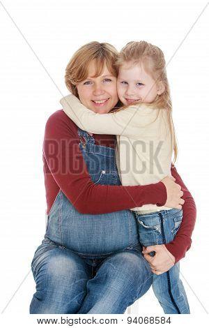 Pregnant mom hugs beloved little daughter , close-up