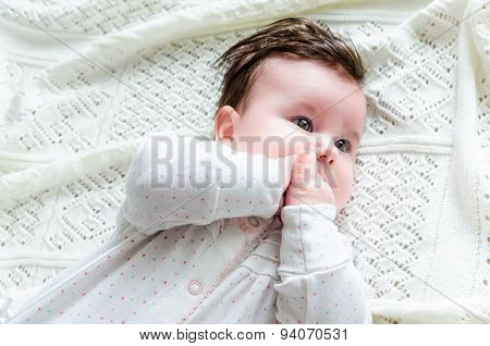 Cute Newborn Baby Girl In Romper Suit Lying On Woolen Blanket