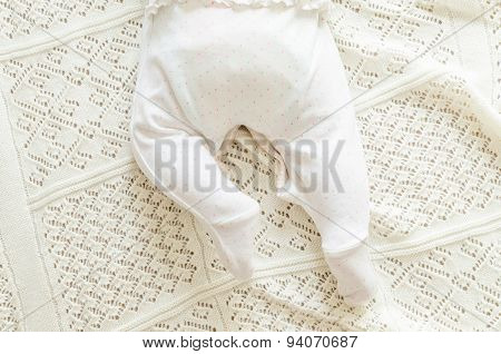 Tiny Little Newborn Baby's Feet In Spotted Romper Suit On Woolen Blanket