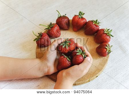 The Child Holds A Large Ripe Strawberries