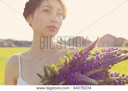 beautiful sexy girl with a sweet lupine flowers with beautiful hair in a white sundress standing in