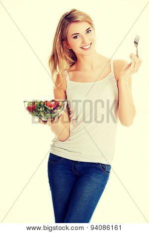 Smiling woman eating healthy salat