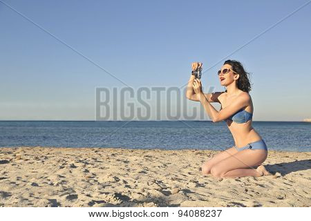 Woman taking pictures at the seaside