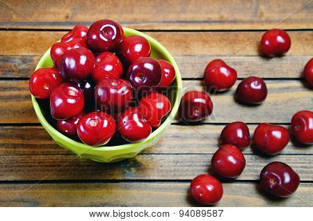 Bowl With Cherries On Wooden Table