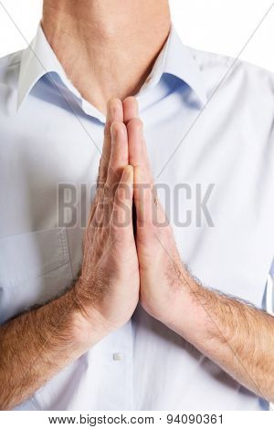 Close up on male hands clenched to pray.