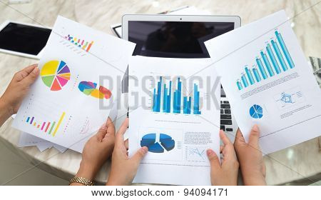 Group of business people pointing at business document during meeting