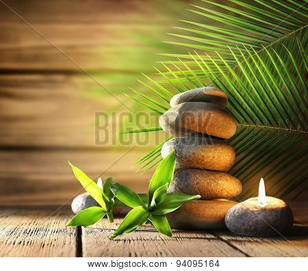 Spa stones, candle on wooden background