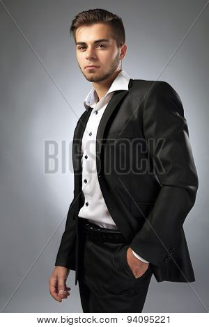 Handsome businessman on gray background