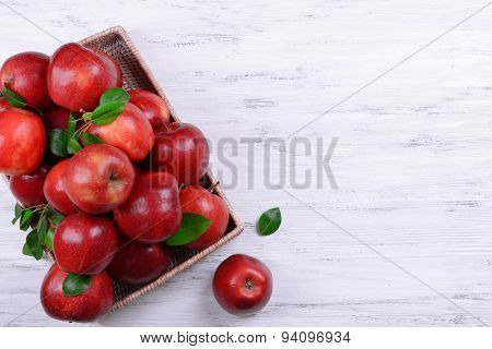 Ripe red apples in crate on wooden background