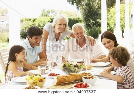 Family eating lunch outside in garden