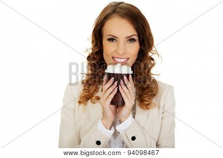 Business woman drinking coffee from paper cup.