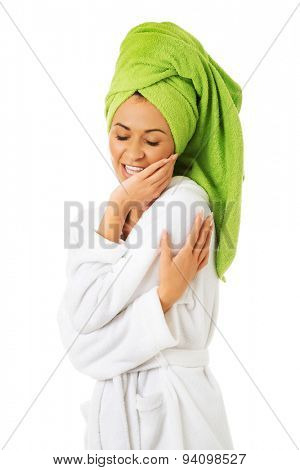 Happy spa woman in bathrobe touching her face.