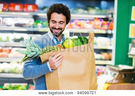 Man looking at his shopping bag in a grocery store