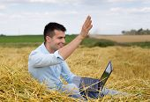 image of waving hands  - Young attractive man with laptop sitting on haystack at farmland and waving hand to someone - JPG
