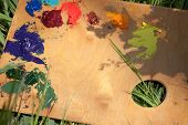 stock photo of paint palette  - Background with a wood palette with oil paint lying on the grass - JPG