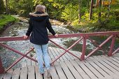 picture of snickers  - Beautiful blond Caucasian teenage girl stands on wooden bridge across small fast river in Finland back view - JPG