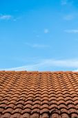 stock photo of roof tile  - Orange tile roof under blue sky with soot from chimney - JPG