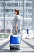 foto of walking away  - Full body portrait of a happy traveling business woman walking away with bag - JPG