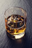 stock photo of scotch  - Glass of scotch whiskey with ice on black stone table - JPG