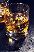 picture of scotch  - Glasses of scotch whiskey with ice on black stone table - JPG