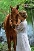 picture of horse face  - Woman standing with horse near lake and touching horse face with her forehead - JPG