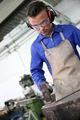 stock photo of ironworker  - Young man in ironworks training working on steel - JPG
