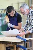 picture of wood pieces  - Young apprentice with teacher working on piece of wood - JPG