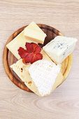 pic of cheese platter  - edam parmesan and brie cheese on wooden platter over wooden table - JPG