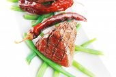 image of veal  - served grilled beef veal fillet entrecote on a white plate with peppers and green peas on long plate isolated on white background - JPG
